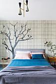 Doppelbett vor Tapete mit Baummotiv