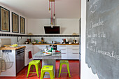 Concrete table and bright green stools in front of L-shaped kitchen counter