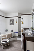 Washstand with twin sinks and bathtub in white-tiled bathroom