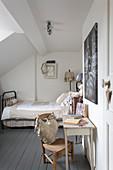Bett, Wandtisch und Stuhl im Gästezimmer