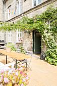 Sonniger Innenhof mit Gartentisch und Rankpflanzen