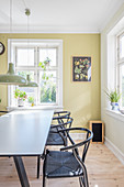Lime-green wall and designer chairs in sunny dining room