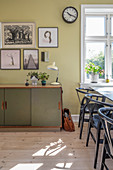 Vintage sideboard, gallery of pictures and designer chairs in dining room