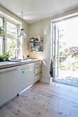 Lichtdurchflutete Küche mit hellem Holzboden und Gartenzugang
