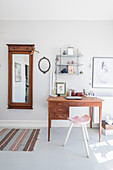 Old mirror on wall and desk in bright room with grey floor