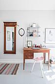 Alter Wandspiegel und Schreibtisch im hellen Raum mit grauem Boden