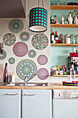 Circular mandalas on wall and shelves on wall in green niche above kitchen counter