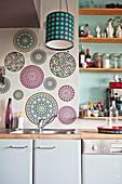Kreisförmige Wandtattoos und Regalbretter an grüner Wand über Küchenzeile