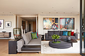 Grey sofa set, designer coffee table and large photos on wall in elegant lounge