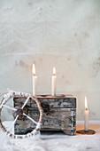 Holzschatulle und brennede Kerzen
