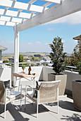 Elegante Stühle, Tisch und Kübelpflanzen auf Dachterrasse