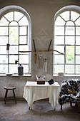 Tisch mit Schalen und Federsammlung, Sessel mit Felldecke und Hocker vor Rundbogenfenster im Loft