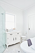 Washstand with countertop sink below window, toilet and free-standing bathtub in white bathroom