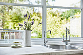 Jug of lavender flowers next to sink integrated in kitchen counter below window