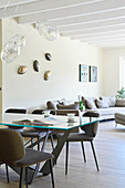 Glass table, upholstered chairs, designer lamps and sofa set in open-plan interior