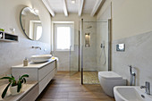 Washstand, shower cabinet and bidet in renovated bathroom
