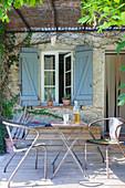 Tisch und Metallstühle vor Fenster mit blauem Fensterladen auf Holzterrasse mit Pergoladach