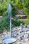 Outdoor shower against stone wall in garden