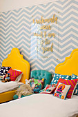 Two yellow beds with pillows and soft toys, zig-zag wallpaper and message on the wall