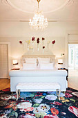 Elegant bedroom with white double bed, clothes bench, chandelier and flowers on the wall