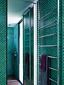 Towel dryer and mirror wall in the shower with green mosaic tiles