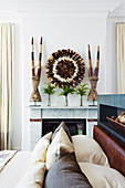 View of mantelpiece over bed with tribal pillows