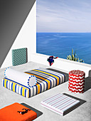 Mattress, seat cushion and bolster with colorful covers on terrace with sea view