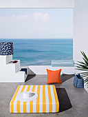 Mattress and pillows with colorful covers on terrace with sea view