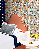 Bed with striped headboard against wall with designer wallpaper