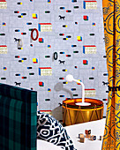 Designer wallpaper with gymnastic rings, drum as a bedside table next to bed in the children's room