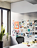 Postcard collection on pin board, white desk with black chair in study