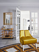 Gold-colored designer chair on carpet, mirror and bar trolley in matching colors in the background