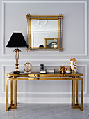 Table lamp on console with gold-colored frame and glass top, above wall mirror with gold frame