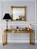 Tischlampe auf Konsole mit goldfarbenem Gestell und Glasplatte, darüber Wandspiegel mit Goldrahmen