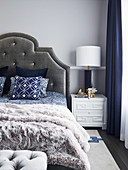 Double bed with bed headboard on light gray wall and elegant bedside table with table lamp