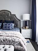 Doppelbett mit Bettkopfteil an hellgrauer Wand und elegantes Nachtkästchen mit Tischleuchte
