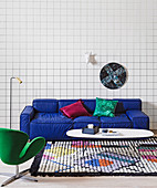 Blue sofa in front of wallpaper with grid pattern, coffee table on colorful carpet and replica of classic chair