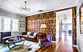 Leather sofa and floor lamp in front of vintage library wallpaper, purple upholstered chairs and coffee table in living room