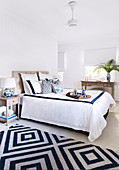 Double bed in the bedroom with white and blue accessories, antique console table in the background
