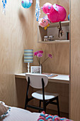 Wood-clad wall with integrated desk and shelf in girl's room