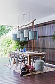 Langer Holztisch mit Klassikerstühlen, darüber Pendelleuchten auf überdachter Terrasse, Mädchen spielt mit dem Hund