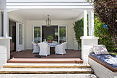 Round table with white rattan armchairs on covered terrace
