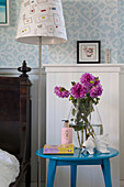 Glass vase with pink dahlias on a blue bedside table next to a standard lamp