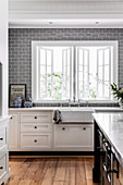 White kitchen unit and gray wall tiles in the kitchen with window