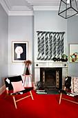 Zwei Stühle auf rotem Teppich vor Kamin im Wohnzimmer mit hellgrauen Wänden und Stuck