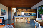 Kitchen with wooden fronts in an open living room with concrete floor