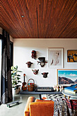 Mask collection, pictures, cones and musical instruments, in the foreground coffee table and leather couch in the living room
