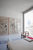 Large comic-style artworks in minimalist bedroom