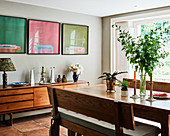 Three artworks on wall above retro sideboard in dining room