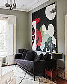 Abstract painting above black velvet sofa in living room